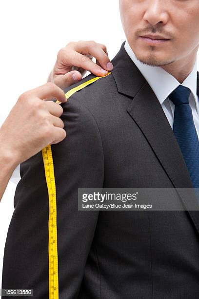 Fashion designer taking a measurement of  businessman