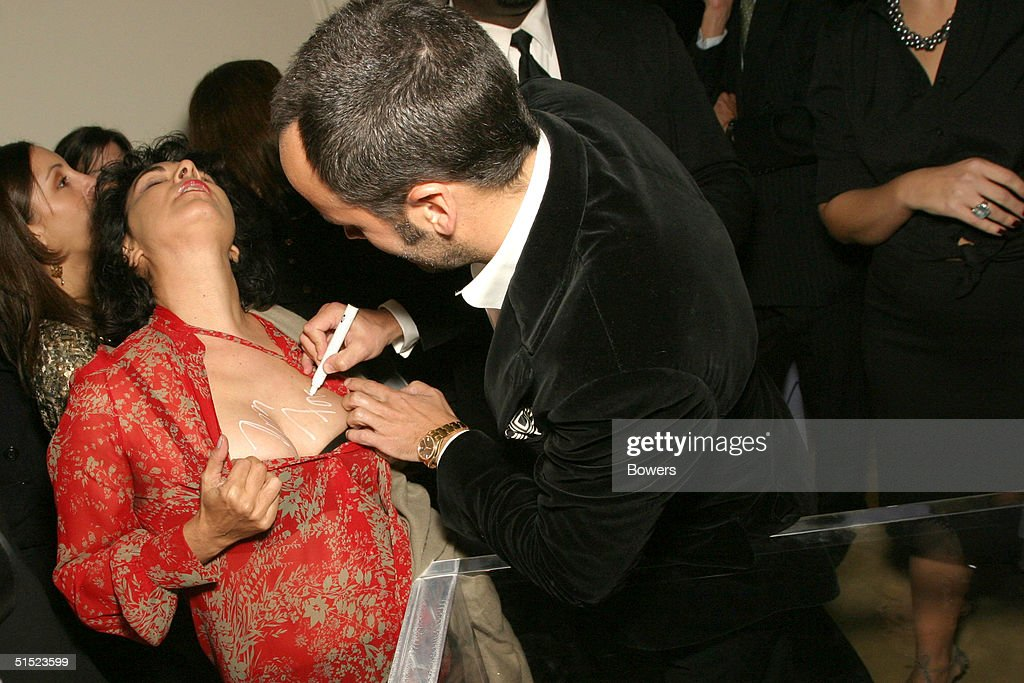 Fashion designer Tom Ford signs Tracy Moffatt at the book launch party for 'Tom Ford:Ten Years' at Bergdorf Goodman October 20, 2004 in New York City. (Photo by Bowers/Getty Images).