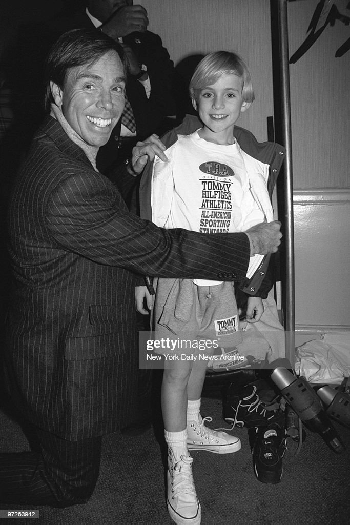 Fashion designer Tommy Hilfiger helps soap star Tyler Noyes get ready to model his clothes at a fashion show for boyswear