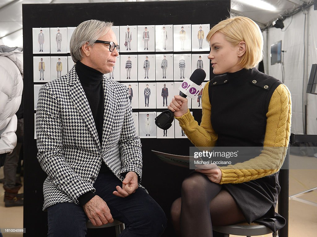Fashion designer Tommy Hilfiger is interviewed by model Jessica Stam backstage at the Tommy Hilfiger Men's Fall 2013 fashion show during Mercedes-Benz Fashion Week at Park Avenue Armory on February 8, 2013 in New York City.