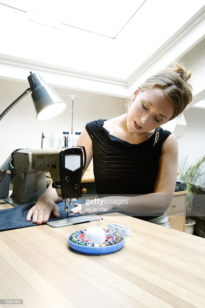Fashion designer using sewing machine, close-up : Stock Photo