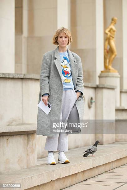 Fashion designer Vika Gazinskaya wears a gray jacket with a baby blue donald duck cartoon tshirt and loose light blue trousers and white Reebok...