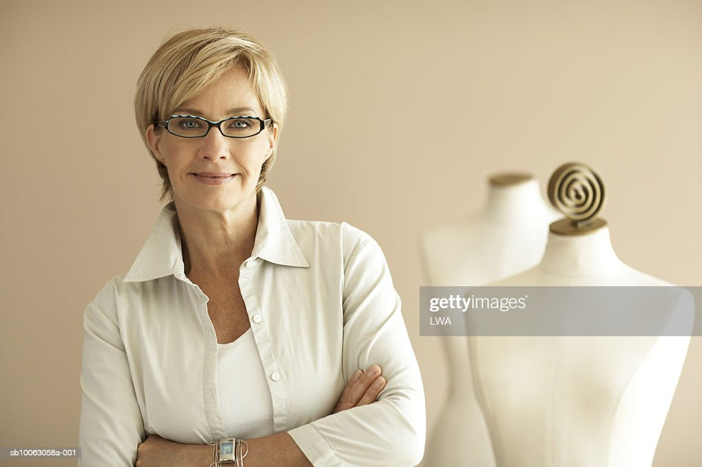 Fashion designer with arms crossed by mannequin, smiling, portrait : Stock Photo