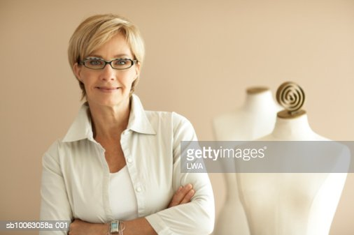 Fashion designer with arms crossed by mannequin, smiling, portrait : Stockfoto
