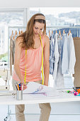 Beautiful female fashion designer working in studio