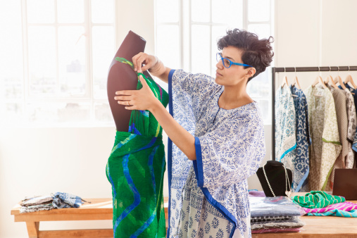 Fashion designer working on dress on dummy .