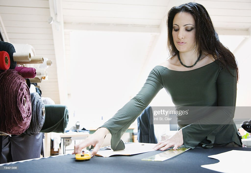 Fashion designer working with pattern in studio : Stock Photo