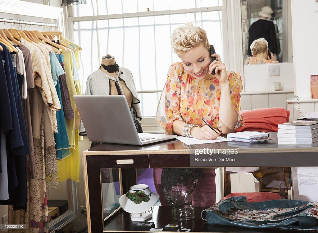Fashion designer writting notes while on phone. : Stock Photo