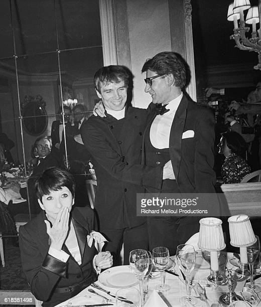 Fashion designer Yves Saint Laurent (R) attends a banquet with ballet dancers Rudolph Nureyev and Zizi Jeanmarie. They are celebrating the launch of Saint Laurent's latest fragrance, Kouros, at the Opera Comique in Paris.