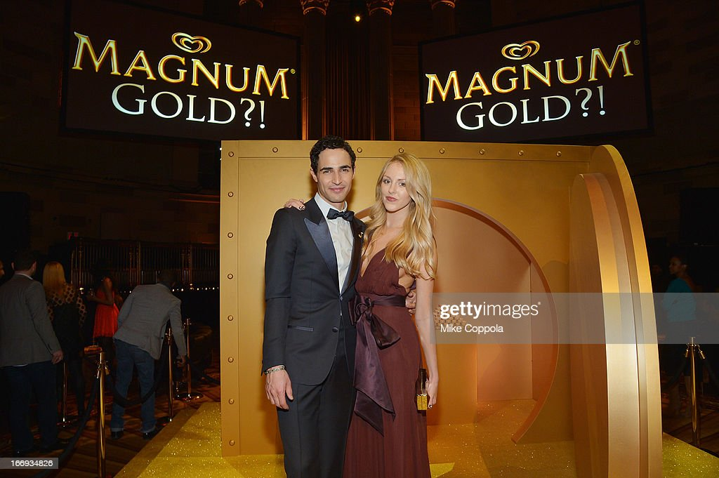 Fashion Designer Zac Posen and fashion blogger Shea Marie pose in front of the MAGNUM Gold?! vault at the 'As Good As Gold' MAGNUM Gold?! Film Premiere on April 18, 2013 in New York City.