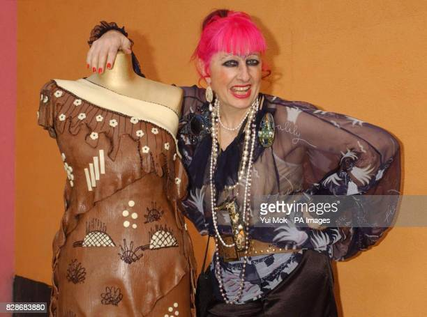 Fashion designer Zandra Rhodes poses next to a chocolate dress created by Monsieur JeanClaude Sibret Master Chocolatier at Godiva to mark the opening...