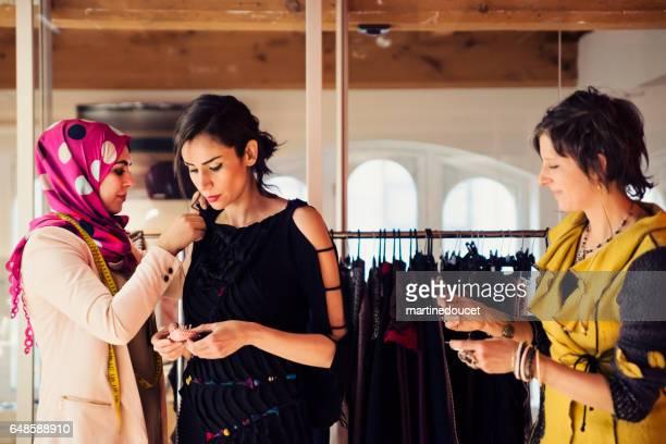 Fashion designers adjusting clothing on female model.