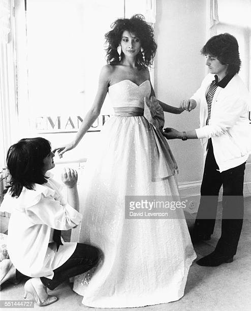 Fashion designers David And Elizabeth Emanuel who designed the wedding dress of Princess Diana of Wales fitting a dress on model Louise Soame 1981