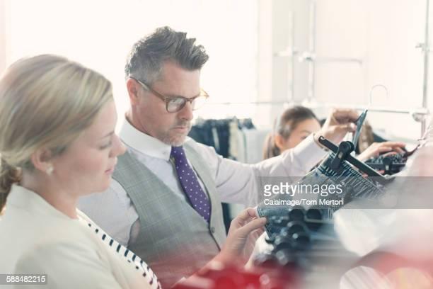 Fashion designers examining clothing