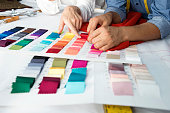 Fashion designers are choosing fabric and color for their new collection.