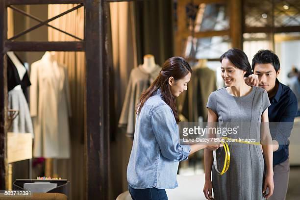 Fashion designers taking measurement of customer