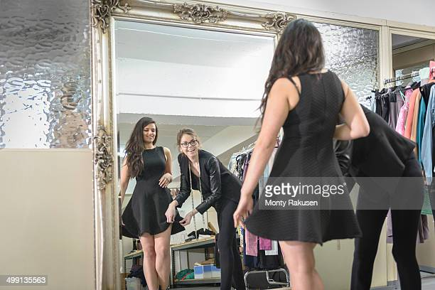 Fashion designers working together in front of mirror in fashion studio