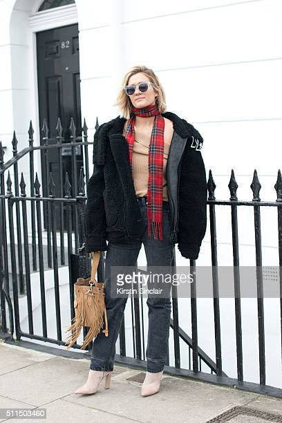 Fashion editor and blogger Adenorah wears Levi's jeans River Island top scarf and bag Zoe Jordan jacket Stella Luna boots and vintage sunglasses on...