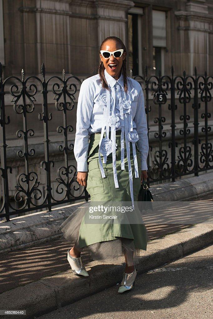 Fashion editor for Garage Magazine Michelle Elie wears Miu Miu sunglasses, Comme Des Garçons skirt, Nicolas Ghesquiere shoes, Prim By Michelle Elie bag on day 2 of Paris Collections: Women on March 04, 2015 in Paris, France.