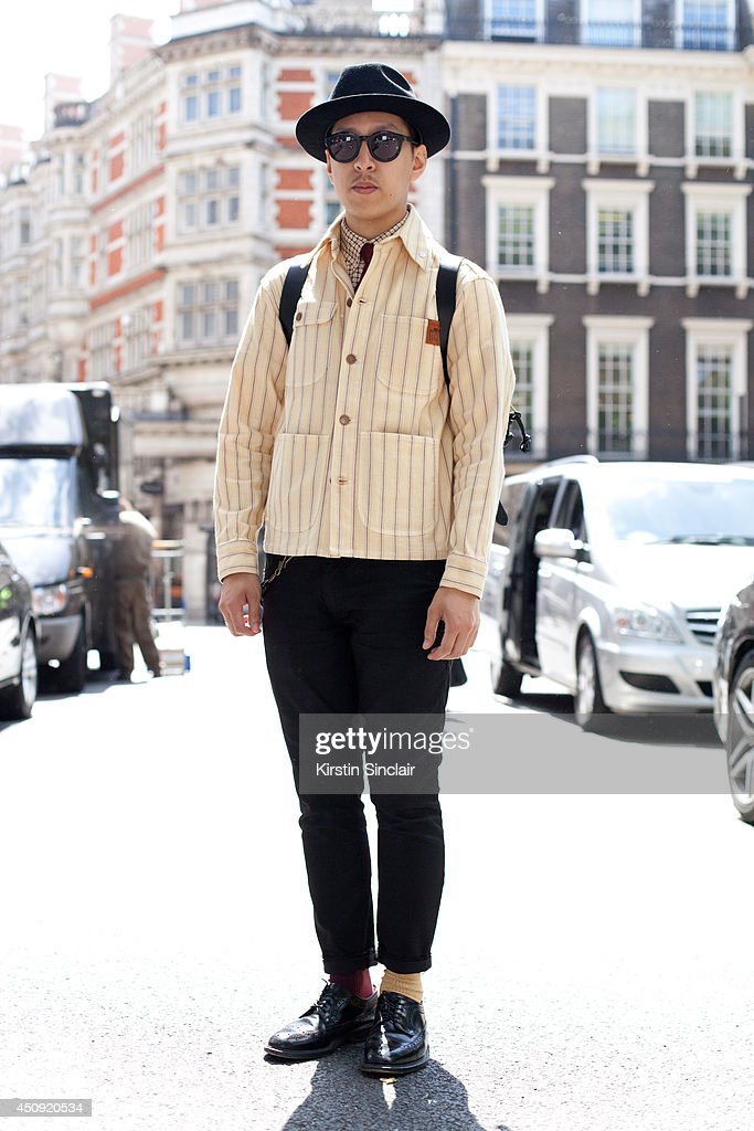 Fashion Editor for Individualism John Jarratt wears a Shaun Gordon tie, Gap trousers, Eye-Respect sunglasses, Brooklyn Circus jacket, Loake shoes, Laird hat and Filson bag on day 3 of London Collections: Men on June 17, 2014 in London, England.