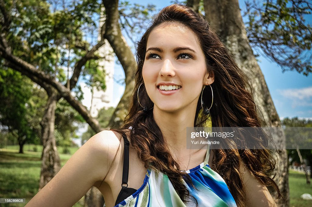 Fashion girl smiling in a park : Stock Photo