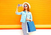Fashion glamour woman takes a picture self portrait on smartphone in the city on a orange background