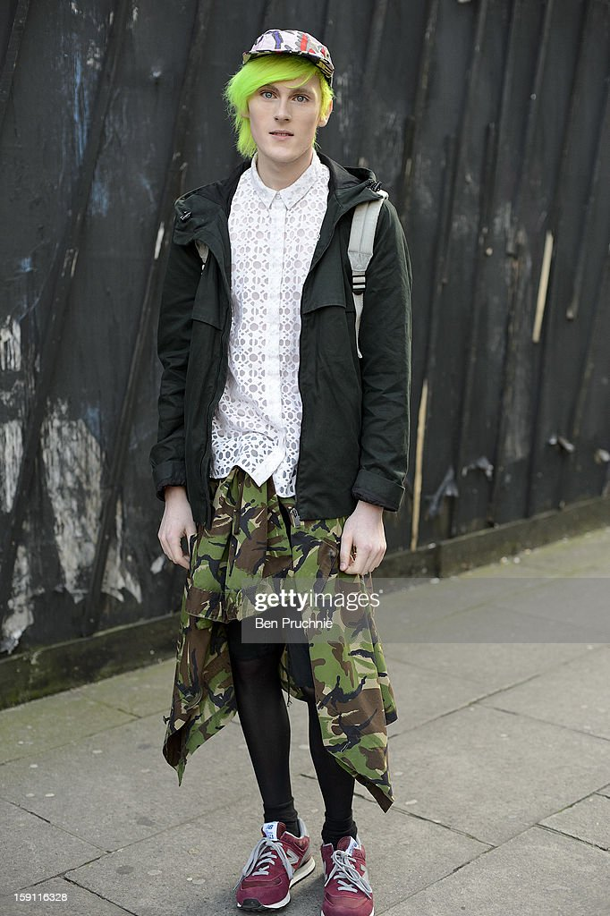 Fashion Intern Daniel 20 poses wearing KTZ Hat, COS Shirt and Jacket, Vintage army surplus bottoms with New Balance shoes at the YMC Catwalk show during London Collections: MEN on January 8, 2013 in London, England.