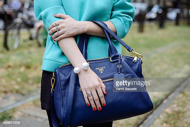 Fashion journalist Li Xin poses wearing a Whistles top and Prada bag on September 17 2014 in Milan Italy