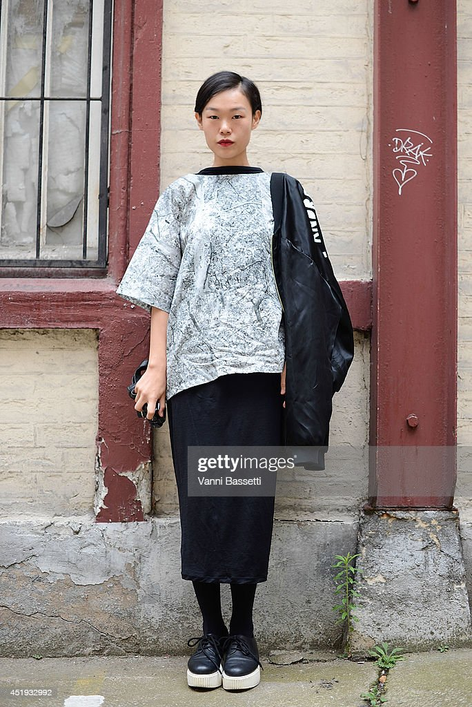Fashion journalist Sun Jeong poses wearing Andrea Crew jacket, Etudes Studio shirt, COS skirt and Karl Lagerfeld shoes before Maison Martin Margiela show on July 9, 2014 in Paris, France.