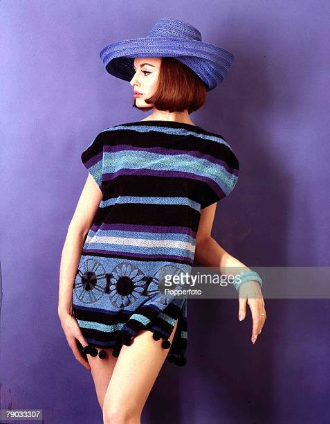Young woman poses in a studio fashion picture wearing a blue summer hat and a boldly stripped chenille tabard with flower details and pom poms...