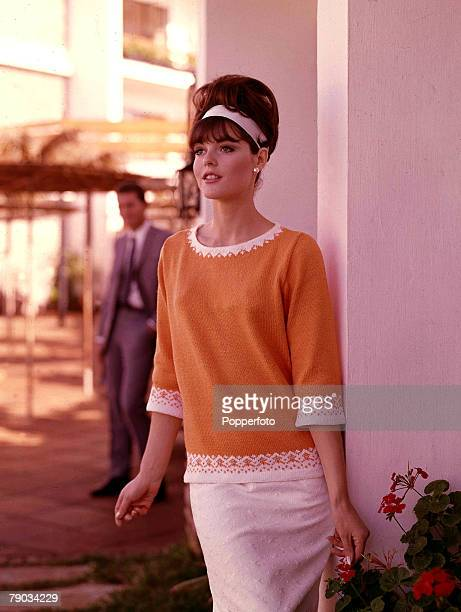 Young woman standing in the shade of a modern building on a sunny day while a smartly dressed man waits behind She is wearing a finely knitted orange...