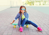 Fashion little girl child sitting on skateboard in city, wearing a sunglasses and checkered shirt