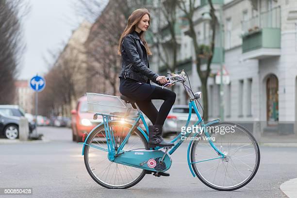 Fashion model Anna Wilken on her bicycle wearing Zara jacket dress Buffalo boots on December 10 2015 in Berlin Germany