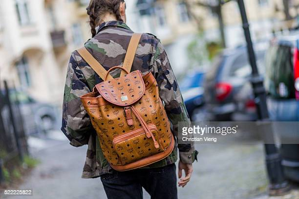 Fashion model Anna Wilken with braid hair wearing a camouflage jacket from NaKd a MCM leather backpack 501 black Levis denim jeans on April 18 2016...
