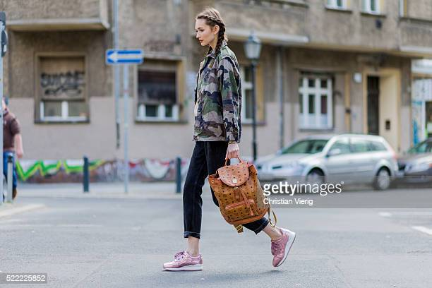 Fashion model Anna Wilken with braid hair wearing a camouflage jacket from NaKd a MCM leather backpack 501 black Levis denim jeans pink Asics sneaker...