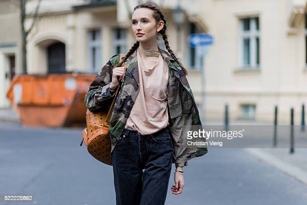 Fashion model Anna Wilken with braid hair wearing a camouflage jacket from NaKd a MCM leather backpack 501 black Levis denim jeans and a nude shirt...