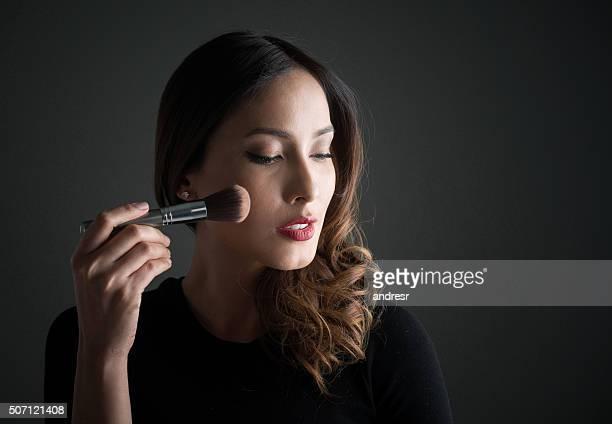 Fashion model applying makeup