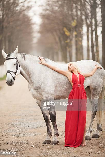 Fashion model in a red dress posing with horse