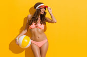 Beautiful smiling woman with brown long curly hair, posing in sunlight in pink bikini and red sun visor, holding beach ball and looking at camera. Three quarter length studio shot on yellow background