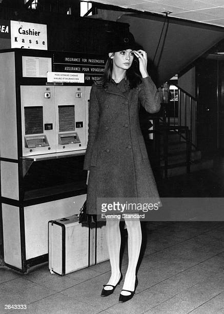 Fashion model Jean Shrimpton standing near an automatic travel insurance machine at the airport