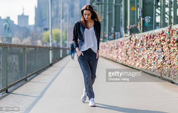Fashion model Jueli Mery at Hohenzollernbruecke with love locks in the background wearing a black jogger pants and white top from Zara black leather...