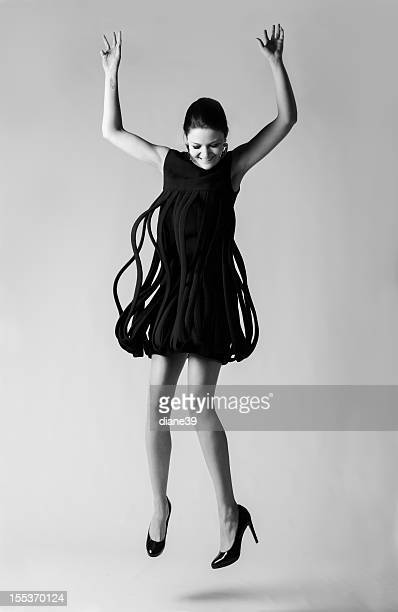 Fashion model jumping in a vintage Avant- Garde dress