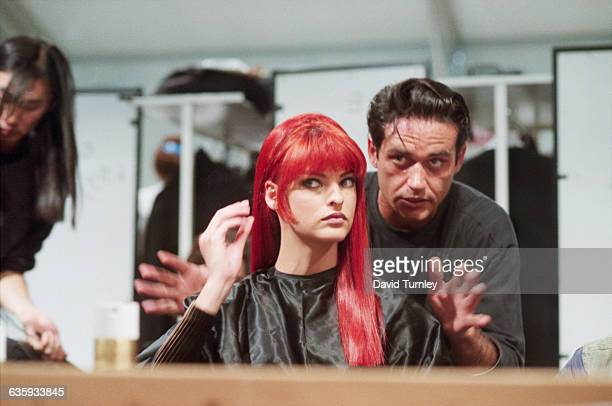 Fashion model Linda Evangelista dons a red wig for a fashion show at the Musee du Louvre in Paris France A celebrity hairstylist Oribe Canales helps...