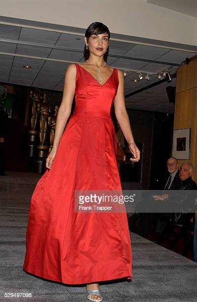 Fashion model Paula wears a Colleen Quen red satin floral back ball gown with Martin Katz pear shaped platinum and diamond drop necklace 87 cts and...
