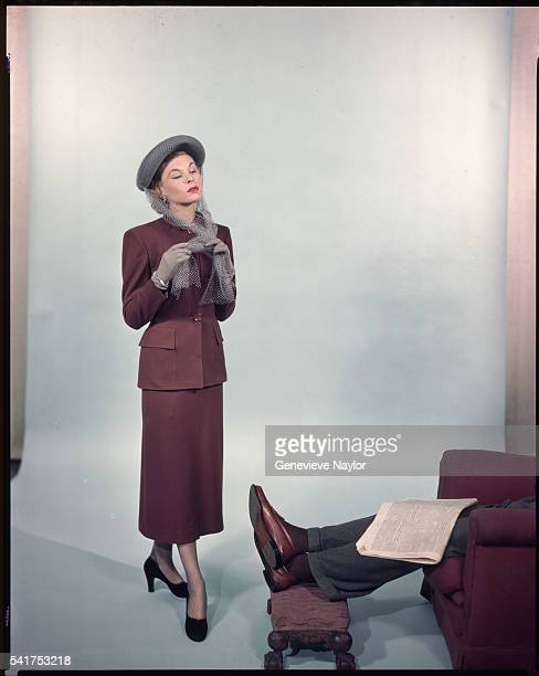 A fashion model unties her hat ribbons and model a suit for McCall's Magazine