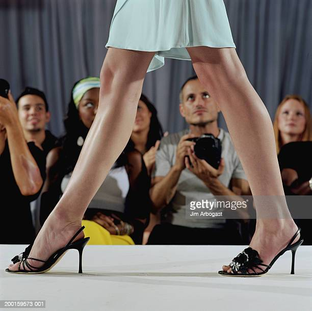Fashion model walking on catwalk, audience in background, low section