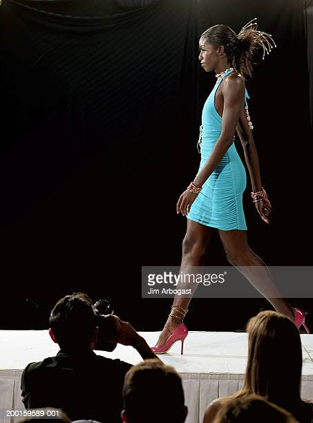 Fashion model walking on catwalk during fashion show, side view