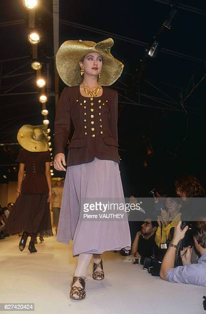 A fashion model wearing a readytowear blazer and skirt with a widebrimmed hat by French fashion designer Lolita Lempicka She is modeling the outfit...