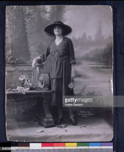 Fashion model wearing a three quarter length dress decorated around the waist with embroidery and a large brimmed hat