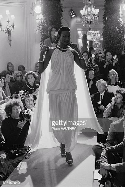 A fashion model wears a sheer white haute couture evening gown and cape by French fashion designer Marc Bohan for the Christian Dior fashion house...